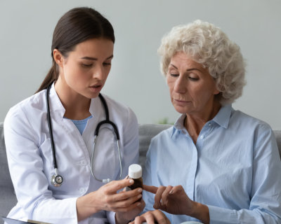 nurse explain antibiotic pill dosage to old woman