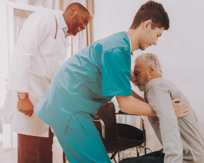a nurse assisting a senior man get to his wheelchair
