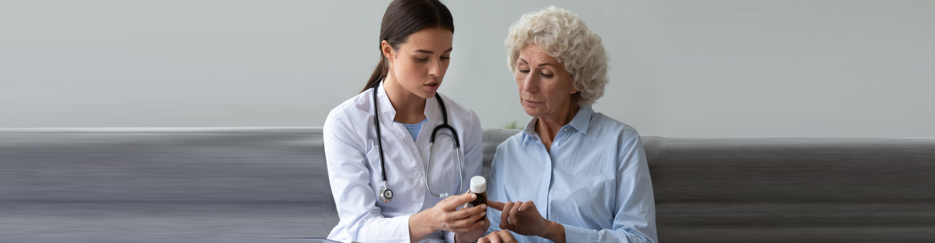 nurse explaining antibiotic pill dosage to senior woman